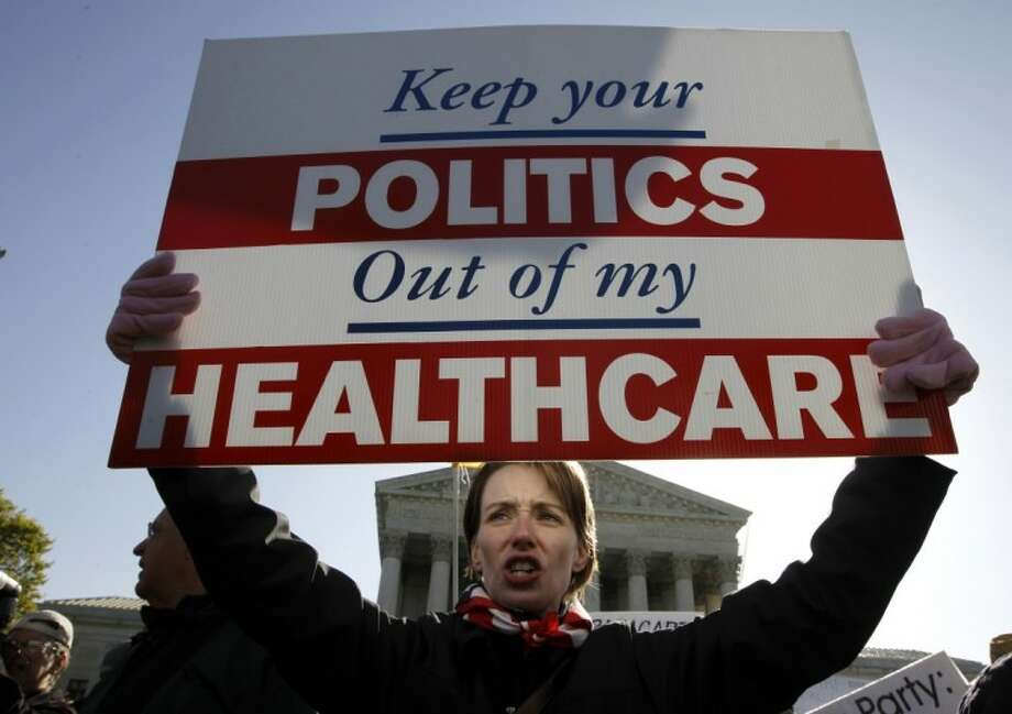 Amy Brighton from Medina, Ohio, who opposes health care reform, rallies in front of the Supreme Court in Washington Tuesday as the court continued arguments on the health care law signed by President Barack Obama. Photo: Charles Dharapak