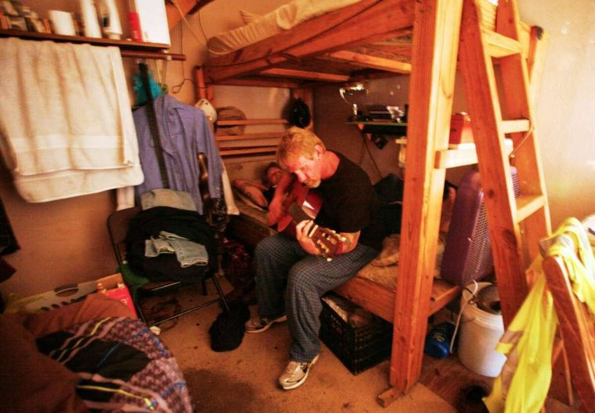 A resident of Bonnie's House plays his guitar at his bunk. Everything he owns is in that corner.