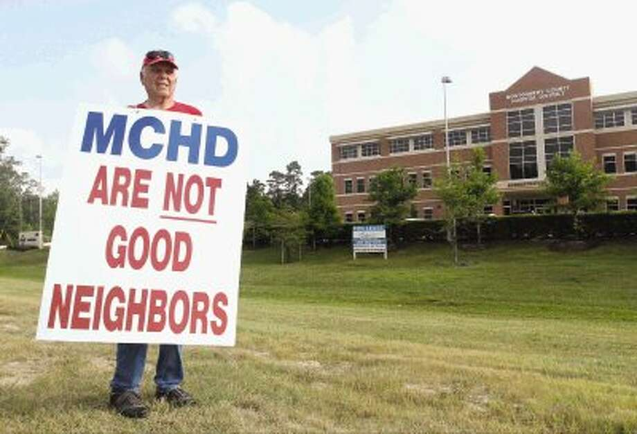 Jim Jones, a Vietnam War veteran, protests outside the Montgomery County Hospital Administration Building Wednesday. Jones said the MCHD building has affected his and his neighbor's quality of life and home value. Photo: Staff Photo By Jason Fochtman / Conroe Courier