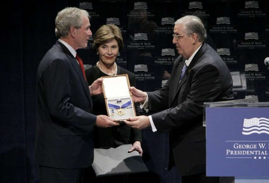 President George W. Bush and wife Laura accepts Cuban freedom activist Dr. Oscar Elias Biscet Gonzalez' Presidential Medal of Freedom, presented by Dr. Angel Gurrido, right, vice president of the Lawton Foundation for Human Rights, Wednesday in Dallas. Photo: Tony Gutierrez