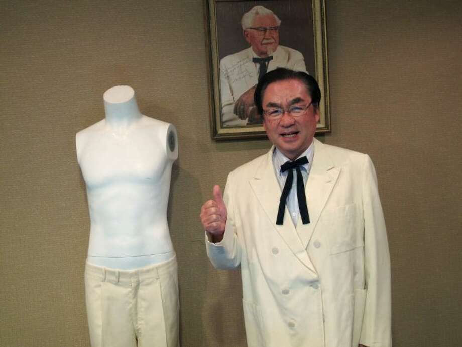 "Masao ""Charlie"" Watanabe, president and chief executive of Kentucky Fried Chicken Japan, stands beneath a portrait of company founder ""Colonel"" Harland Sanders on Saturday, June 22, 2013, at Heritage Auctions in Dallas. Watanabe is wearing Sanders' trademark white suit jacket and black string tie after he purchased them at the auction, which featured other items, including leg irons that restrained abolitionist John Brown. Photo: Angela K. Brown"