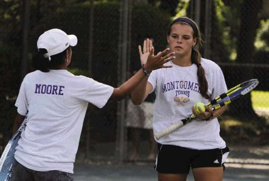 Ericka Richarme give Maddie Moore a high-five during a girls double match in The Woodlands Junior Clay Court Championships at The Woodlands County Club Saturday. Go to HCNPics.com to view and purchase this photo, and others like it. Photo: Staff Photo By Jason Fochtman / Conroe Courier