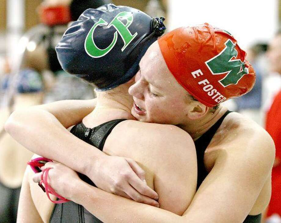The Woodland's Erin Foster hugs College Park's Erin Sosdian after winning the 500-Yard Freestyle at the UIL 5A State Meet in Austin Saturday.