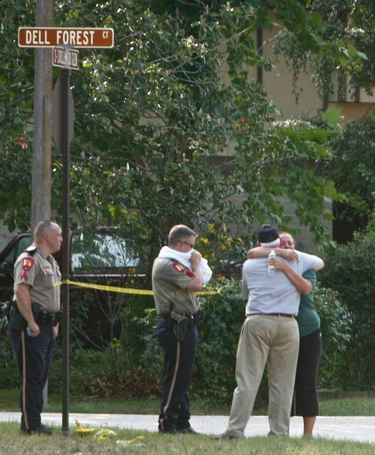Residents embrace on Dell Forest Court in The Woodlands' Village of Panther Creek near the scene of fatal shooting Thursday evening in the Circlewood Glen subdivision. A 37-year-old man allegedly shot and killed his mother at the residence. Photo: Staff Photo By Eric Swist