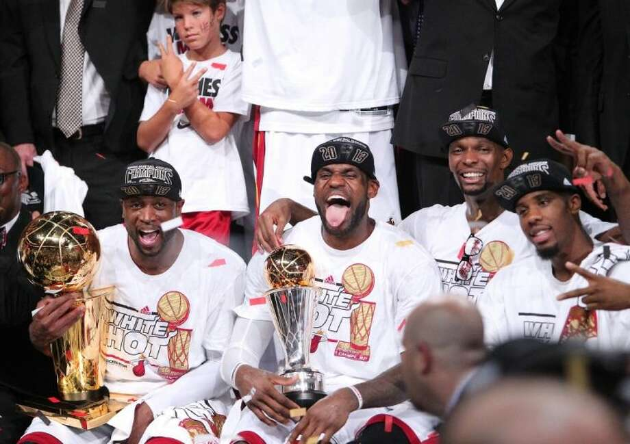 Miami Heat players, from left, Dwyane Wade, LeBron James, Chris Bosh and Norris Cole celebrate after the Heat defeated the San Antonio Spurs 95-88 to win Game 7 of the NBA Finals on Thursday in Miami. Photo: David Santiago