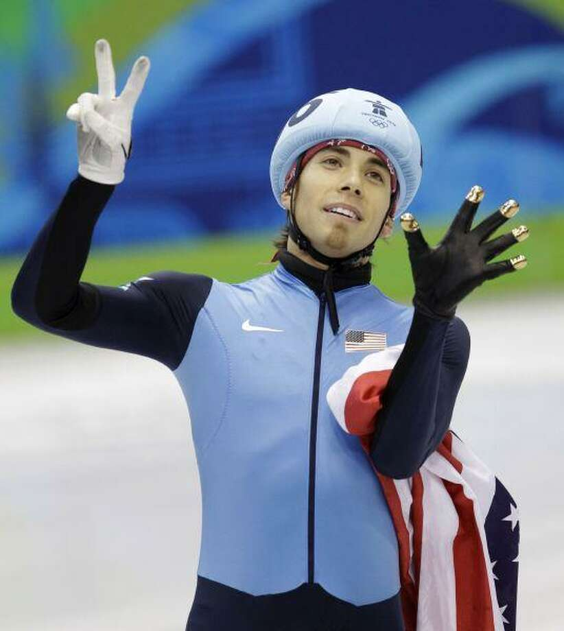 USA's Apolo Anton Ohno gestures with seven fingers, the number of Olympic medals he has won, after winning the bronze medal for the men's 1000m short track skating competition at the Vancouver 2010 Olympics in British Columbia Saturday. / AP2010