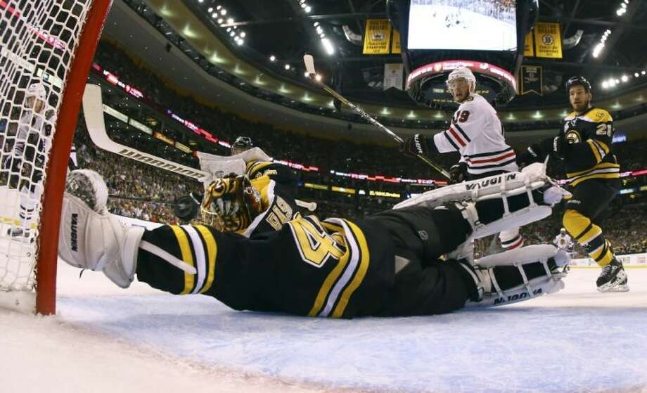 A shot by Chicago Blackhawks right wing Patrick Kane, left, sails over the arm of Boston Bruins goalie Tuukka Rask during the second period of Game 4 of the Stanley Cup Finals on Wednesday in Boston. The goal gave a 3-1 lead to Chicago, which won 6-5 in overtime to even the series 2-2. Photo: Harry How