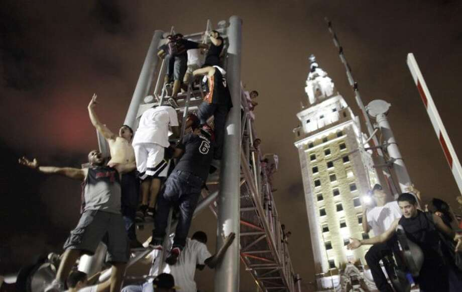 Miami Heat fans climb a stanchion outside American Airlines Arena in Miami on Thursday while celebrating after the Heat won Game 7 of the NBA Finals against the San Antonio Spurs 95-88 to claim their second straight title. Photo: Javier Galeano