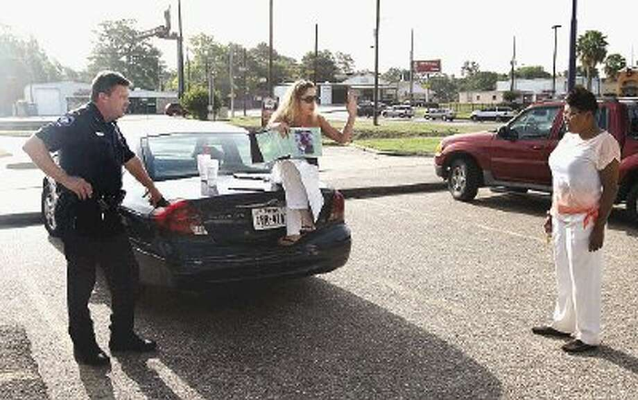 Patrol Officer Steve Hurd, with the Conroe Police Department, left, looks on as Stacy Runyon tells her story about an alleged prescription error to a passerby while picketing a local doctor.