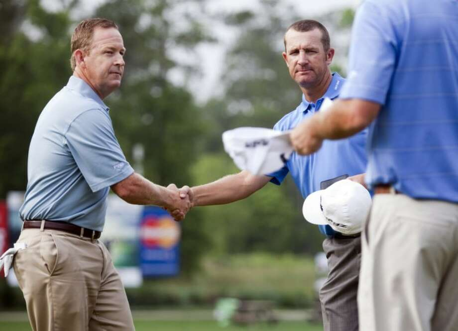 Jeff Maggert, left, shakes hands with David Mathis after finishing the second round in the Houston Open golf tournament, Saturday in Humble. Photo: Eric Kayne