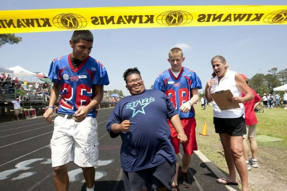 Christopher Solomon of the Conroe Stars crosses the finish line of the 50-Meter Dash with volunteers John Martinez and Devan Herter during the Special Olympics Saturday at Oak Ridge High School. Photo: Karl Anderson