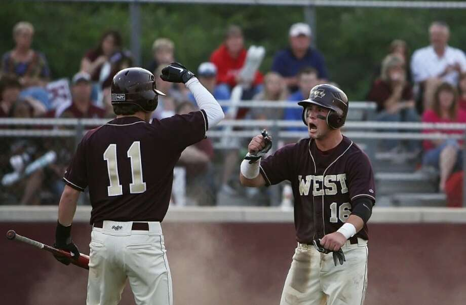 Magnolia West's Jesse Slaughter, right, celebrates a run with teammate Cameron Stanton during Friday night's game against Magnolia at Magnolia High School.