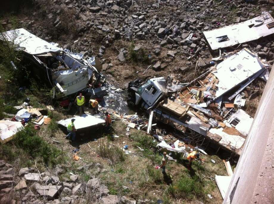 Officials work the scene of a Minnesota-bound motor home on Sunday in a ravine off Interstate 35 in northeast Kansas. The Kansas Highway Patrol said the northbound Freightliner motor home was carrying 18 people and pulling a trailer when the driver lost control at 9 a.m. Sunday and crashed into the ravine. Five were killed. Photo: Anonymous