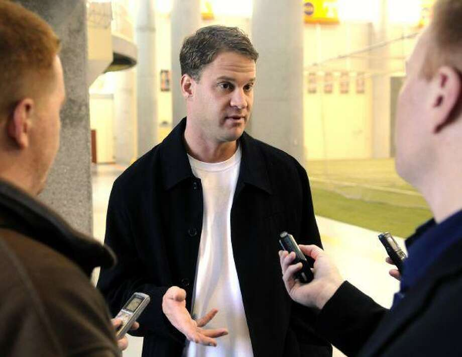 Former University of Tennessee football coach Lane Kiffin talks to reporters on his way out of the University of Tennessee Neyland-Thompson Sports Complex Wednesday in Knoxville, Tenn. Kiffin abruptly left Tennessee after one season Tuesday night to return to USC, where he was an assistant coach for six years before embarking on one of the strangest, swiftest and rockiest journeys in recent coaching history. / AP2010