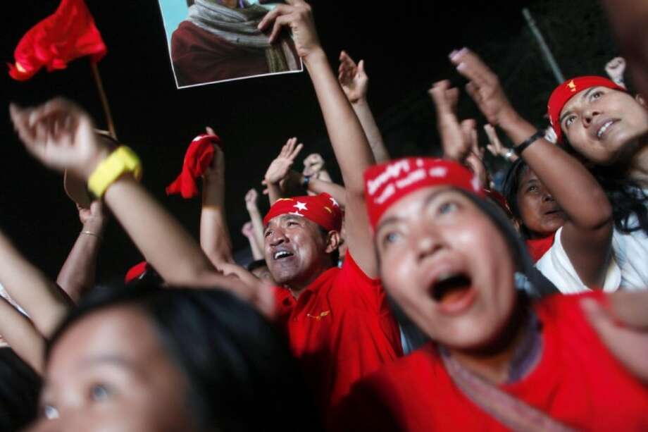 Aung San Suu Kyi's National League for Democracy supporters cheer after the party's announcement outside the party headquarters in Yangon, Myanmar, Sunday. Supporters of Suu Kyi erupted in euphoric cheers Sunday after her party announced that she had won a parliamentary seat in the landmark election, setting the stage for her to take public office for the first time. Photo: Anonymous