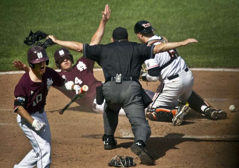 Mississippi State's Hunter Renfroe, second from left, scores the go-ahead run in Saturday's CWS game against Oregon State. MSU won 5-4. Photo: Ross William Hamilton