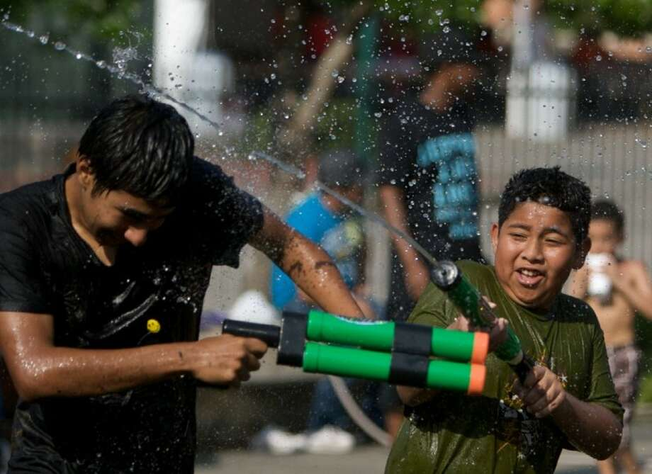 Children play with water guns in the splash zone area Saturday during the 9th annual KidzFest in downtown Conroe. Photo: Staff Photo By Eric S. Swist