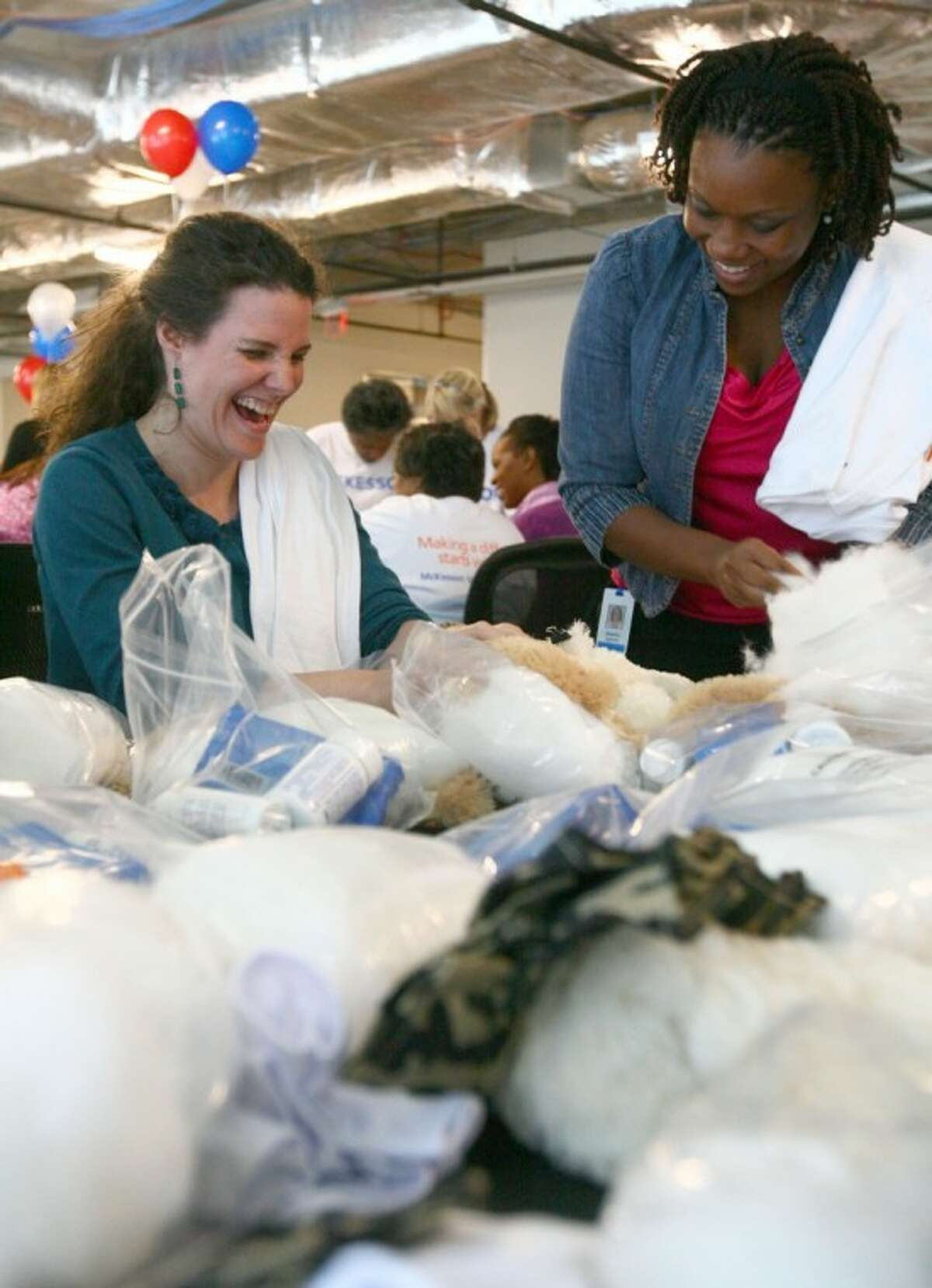 McKesson employees Kally Colburn, left, a product development manager from The Woodlands, and Makafui Agbotui, a projects manager from Houston, assemble care packages at their office in The Woodlands for Operation Gratitude.