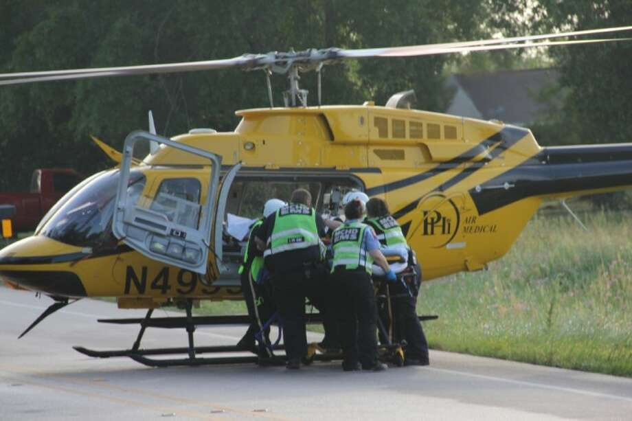 A woman who was driving the vehicle that struck a tree is loaded into a PHI Air Medical Helicopter Monday evening. Her 8-month-old daughter was killed in the wreck near Cut and Shoot. Photo: Photo By James Ridgway, Jr.