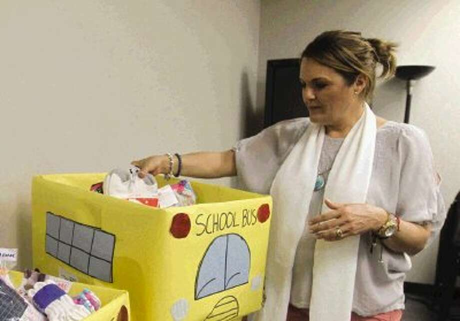 "Ana Sofia Macias drops clothes into a container during the Montgomery County United Way's kickoff for its annual back-to-school ""Socks and Undies"" drive for disadvantaged students in the county. Photo: Staff Photo By Jason Fochtman / Conroe Courier"