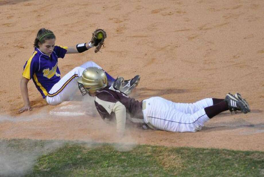 Montgomery shortstop Devon Tunning covers third base as Magnolia West's Heather Peacock dives back into the bag during Thursday night's game.