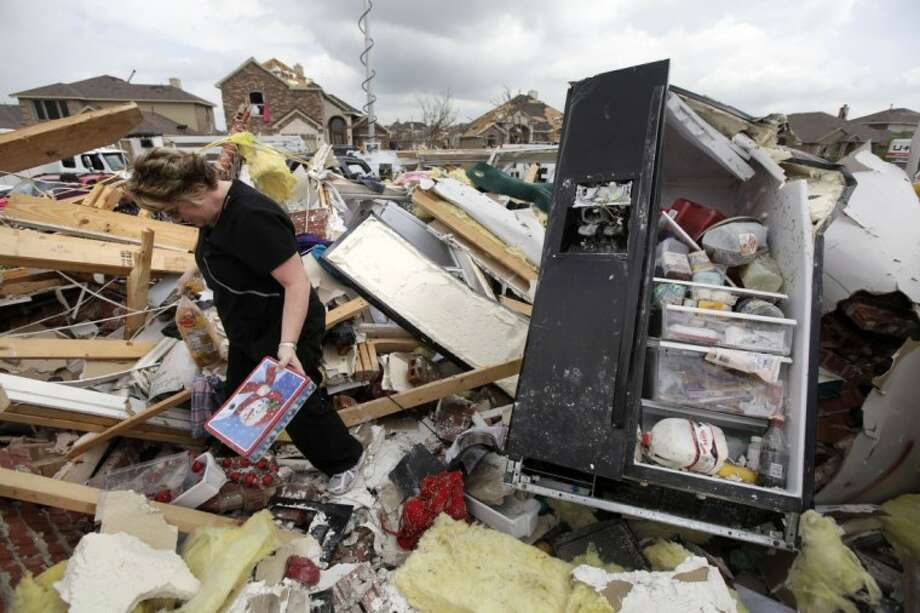 Ashley Quinton walks through the tornado damaged home of her friend Sherry Enochs in hopes of finding personal items that can be salvaged Wednesday in Forney. Enochs was babysitting three children, all under the age of 3, that survived the storm with only minor bumps and scrapes. Photo: Tony Gutierrez