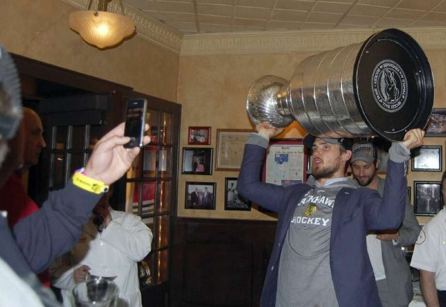 The Chicago Blackhawks' Niklas Hjalmarsson hoists the Stanley Cup for fans inside Harry Caray's on Tuesday morning in Rosemont, Ill. Photo: HOEP