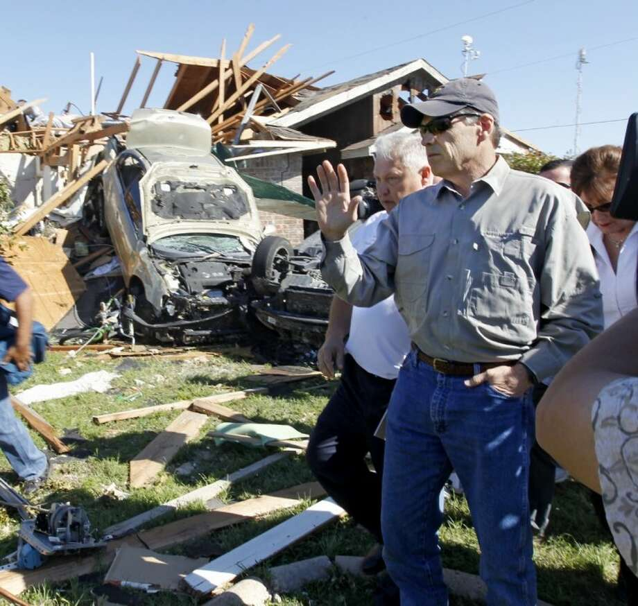 Texas Governor Rick Perry inspects tornado damage in Lancaster Thursday with Lancaster fire chief Thomas Griffith. Tornadoes ripped through the DFW area on Tuesday afternoon. Photo: Erich Schlegel