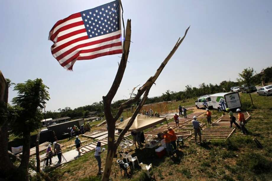 An American flag waves from atop a tornado damaged tree in front of the home of Olga Hernandez Wednesday in Granbury. Photo: Tony Gutierrez