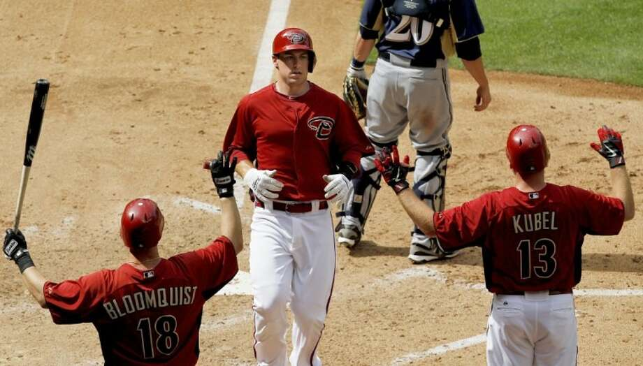 Arizona Diamondbacks' Paul Goldschmidt, middle, scores on a solol home run as teammates Willie Bloomquist (18) and Jason Kubel (13) wait at home plate during the fifth inning of a spring training baseball game against the Milwaukee Brewers on Wednesday, April 4, 2012, in Phoenix. Photo: Ross D. Franklin