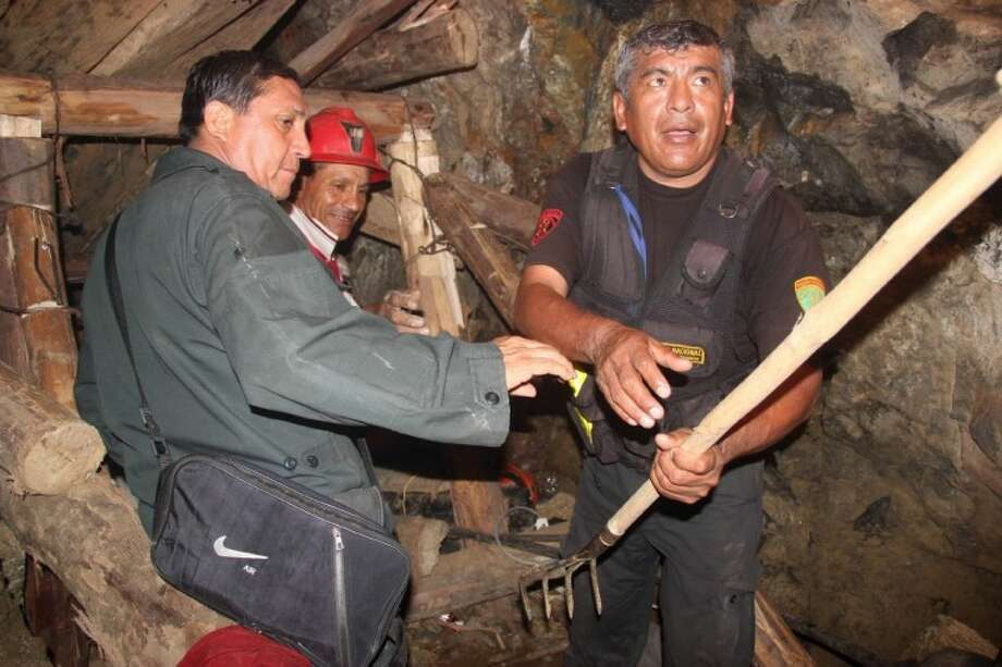 People work in a collapsed mine to rescue trapped miners in Ica, Peru, Saturday. According to Peruvians authorities, nine miners trapped since Thursday in a collapsed mine are being supplied with sports drinks, soup and food while police, firefighters and other workers work to free them. Photo: Anonymous