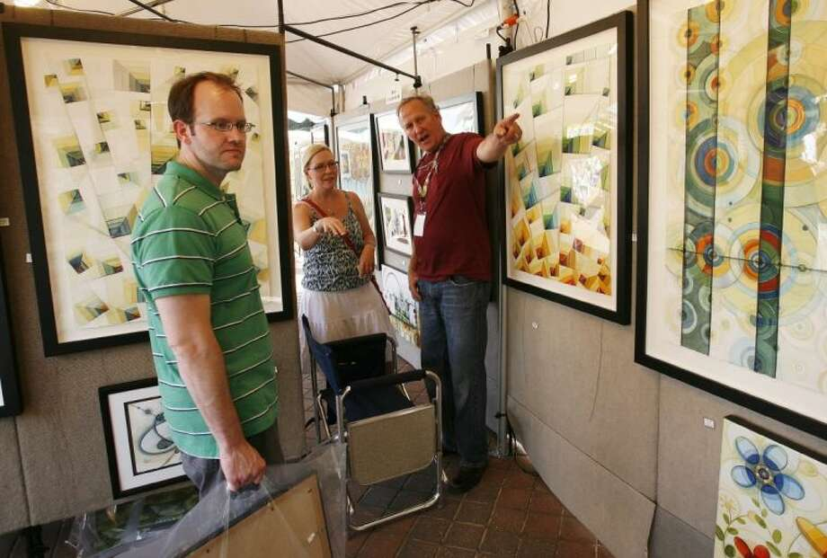 Artist Rick Loudermilk, right, of Austin, talks about some of his work with visitors to his booth Saturday at The Woodlands Waterway Arts Festival. Loudermilk is this year's featured artist.