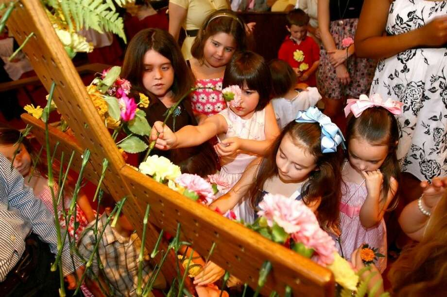 Children place flowers on a cross during an Easter Sunday service at Saint James the Apostle Episcopal Church in Conroe.