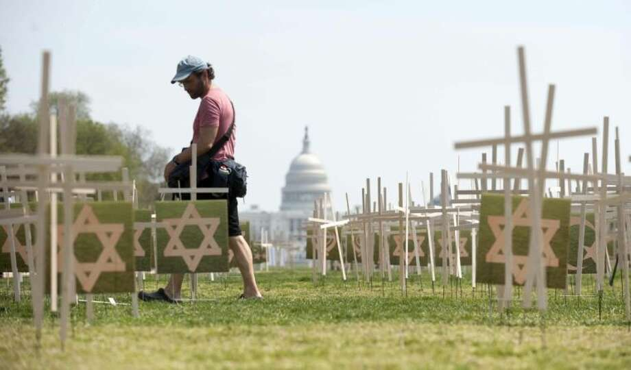 With the Capitol in the background, an unidentified man walks past thousands of grave markers erected in a mock cemetery on the National Mall in Washington Thursday to honor the victims of gun violence. Photo: Kevin Wolf