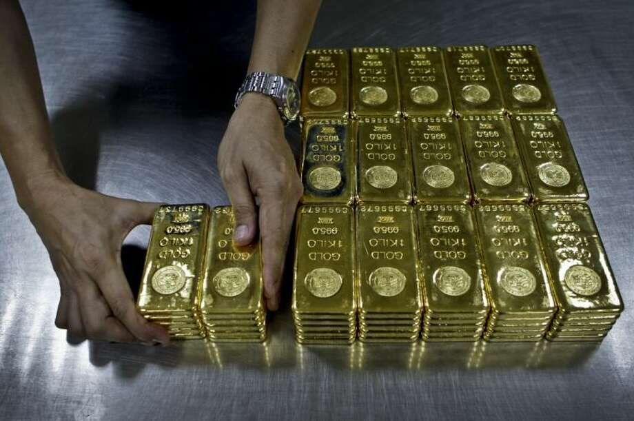 In this Tuesday Oct. 9, 2012 file photo, a technician prepares 1 Kg gold bars of 995.0 purity to pack for delivery at the Emirates Gold company in Dubai, United Arab Emirates. As of Monday, April 15, 2013, gold has plunged more than 10 percent the last two days, suggesting that a decade-long surge in the metal is over. Signs that the U.S. economy is healthier are diminishing gold's appeal as an safe place to invest money. Gold peaked at 1,900 in August 2011 and is now at 1,390. Photo: Kamran Jebreili