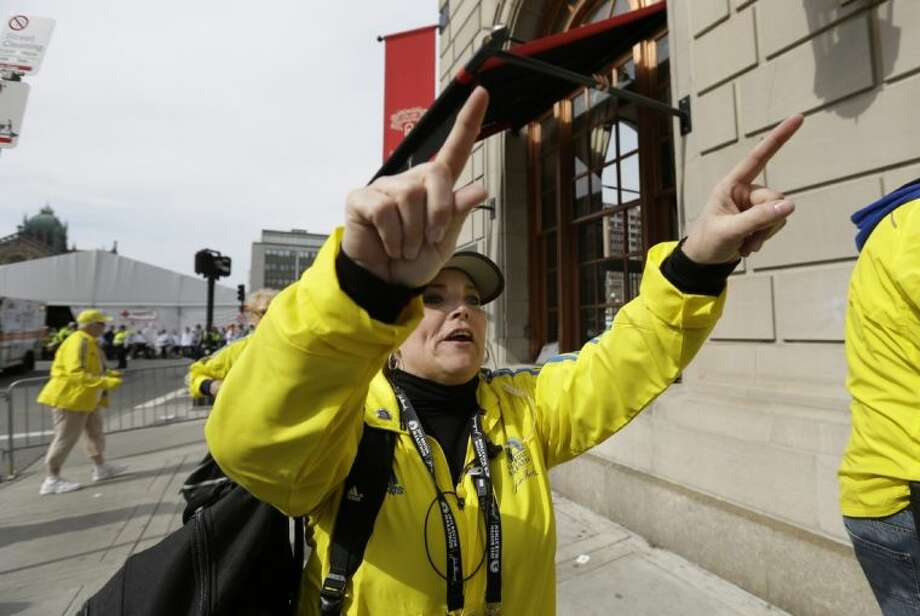 A Boston Marathon volunteer asks people to leave the area outside the Copley Plaza Hotel in the aftermath of two blasts which exploded near the finish line of the Boston Marathon in Boston Monday. Photo: Elise Amendola
