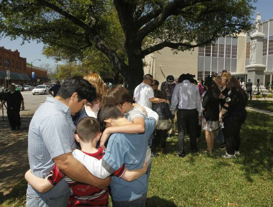 Families pray during a prayer walk around the Kaufman County Courthouse in Kaufman, Texas on Sunday, April 14, 2013. Authorities investigating the deaths of a North Texas district attorney and his wife appear to have narrowed their focus on a former justice of the peace prosecuted by the official for theft earlier this year. Photo: Michael Ainsworth
