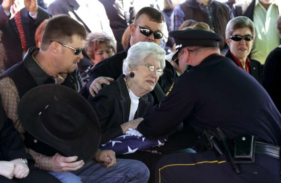 Wyvonne McLelland, mother of Kaufman County District Attorney Mike McLelland, receives a flag from Nathan Foreman during the graveside funeral services for the couple in Wortham Friday.. The Kaufman County District Attorney Mike McLelland and his wife, Cynthia, were found shot to death Saturday in their house near Forney, about 20 miles east of Dallas. No arrests have been made. Photo: LM Otero