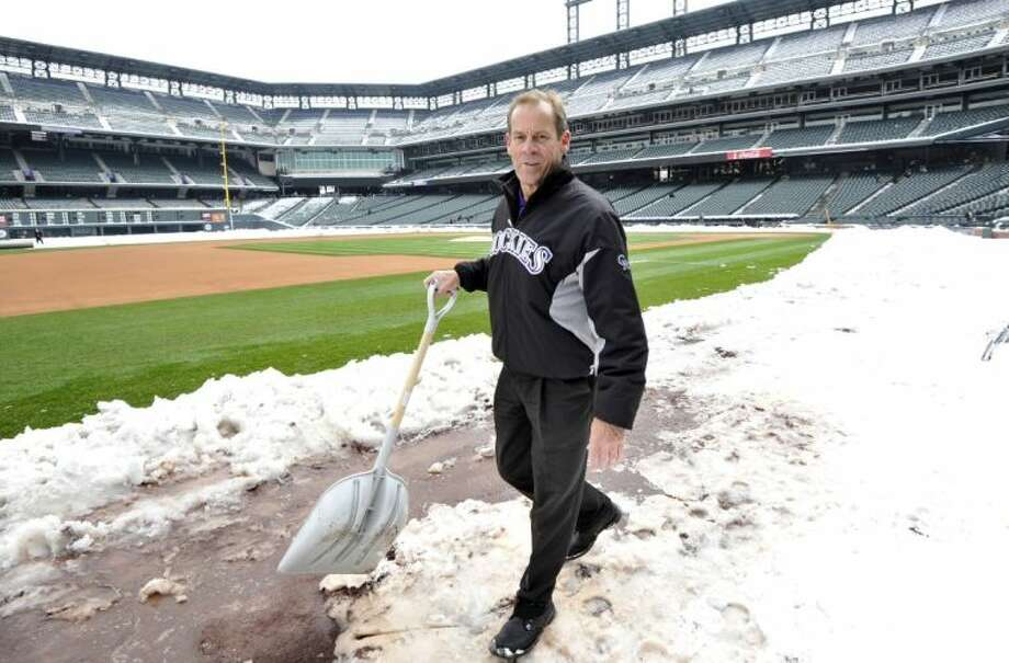 Colorado Rockies owner Dick Monfort shovels snow from the field before the start of a scheduled doubleheader between the New York Mets and the Colorado Rockies on Tuesday in Denver. Photo: JACK DEMPSEY