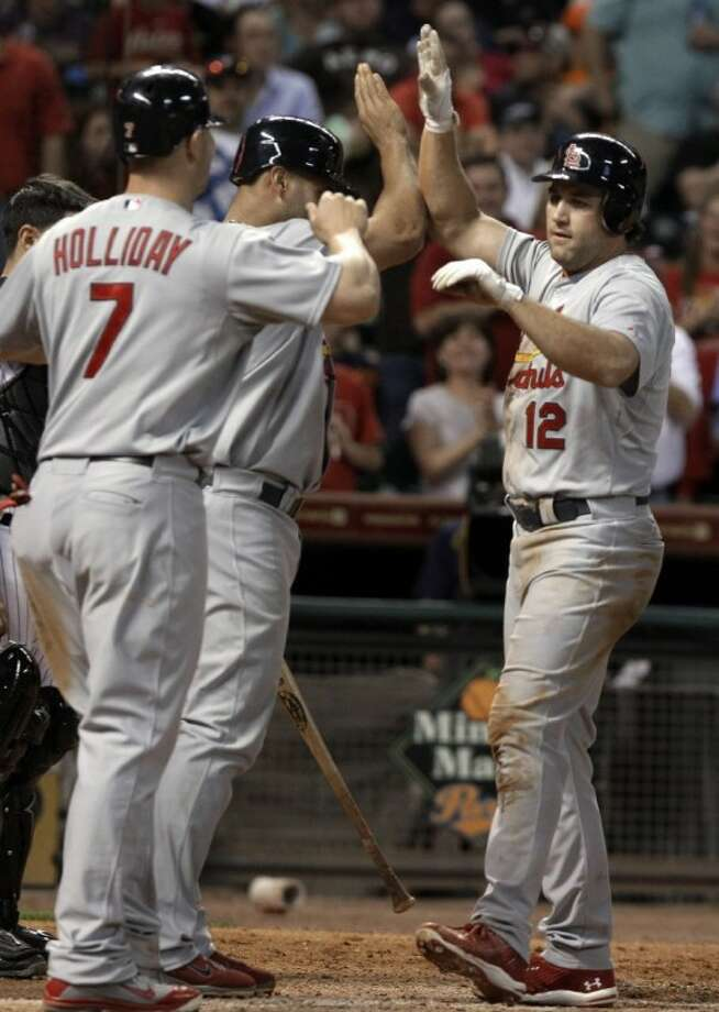 Former Houston Astro and current St. Louis Cardinal Lance Berkman (12) is welcomed to home plate by teammates Matt Holliday (7) and Albert Pujols after hitting a three-run home run in the sixth inning of Thursday's game against the Astros in Houston. Berkman went 4 for 5 with five RBIs and three runs scored.