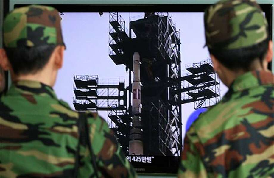 South Korean Army soldiers watch a TV news program which shows North Korea's Unha-3 rocket at Seoul train station in Seoul, South Korea. North Korean space officials moved all three stages of the long-range rocket into position for a controversial launch, vowing Sunday to push ahead with their plan in defiance of international warnings against violating a ban on missile activity. Photo: AP Photo By Ahn Young-joon / AP2012