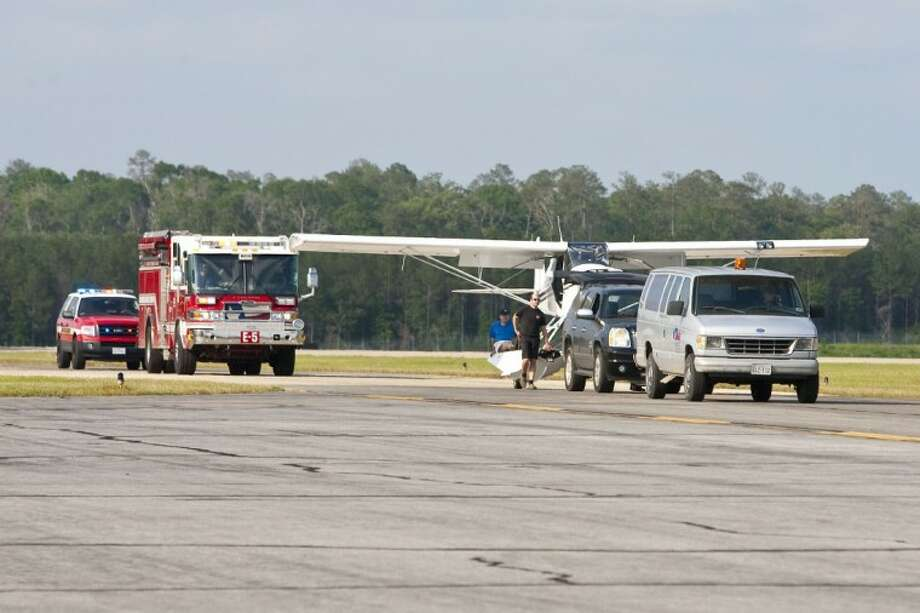 A Super Cub is towed down the runway and followed by Conroe Fire Department engines after experiencing brake failure that resulted in a small grassfire Friday at Lone Star Executive Airport. Photo: Karl Anderson