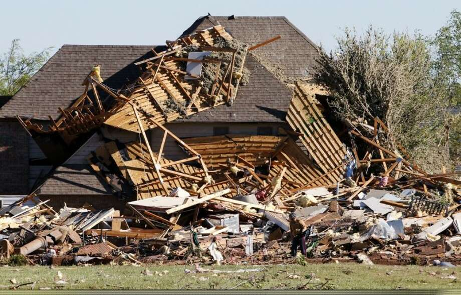 Sue Lord is dwarfed by the debris from her home, which is piled up on the neighbor's home, following a tornado Sunday in Woodward, Okla. Lord was in the home when the tornado struck, but was not injured. Photo: AP Photo