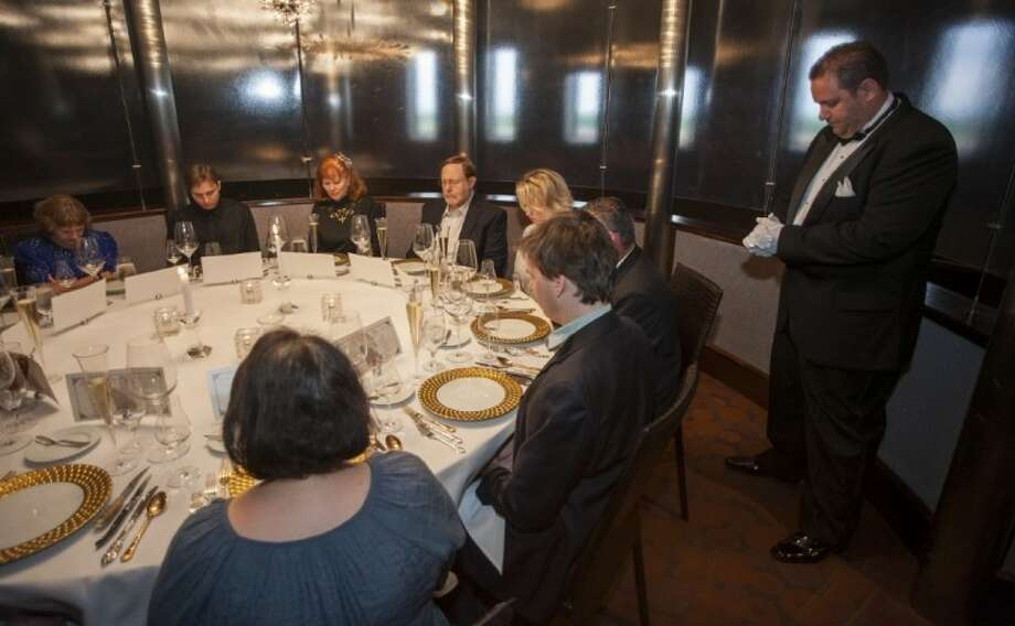 Maitre de Ryan Roberts leads guests in a moment of silence for the 1514 people who died when the RMS Titanic sank during a re-creation of the final first class dinner served on the ship, Saturday, in Houston. The Titanic sank in the North Atlantic Ocean April 15, 1912 after colliding with an iceberg during her maiden voyage from Southampton, England to New York. Photo: AP Photo