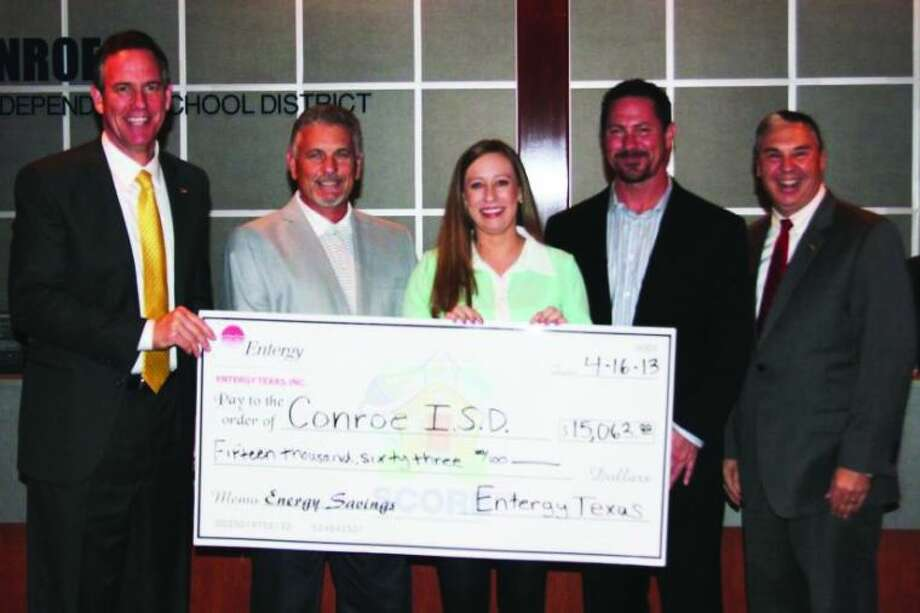 From left, Conroe ISD Superintendent Don Stockton, Entergy Texas Customer Service Manager Victor Enmon, Megan Frisa of CLEAResult, Entergy Texas Program Administrator Phillip Lanier and CISD school board President Ray Sanders show what CISD earned from participating in the Entergy Texas, Inc. SCORE program.