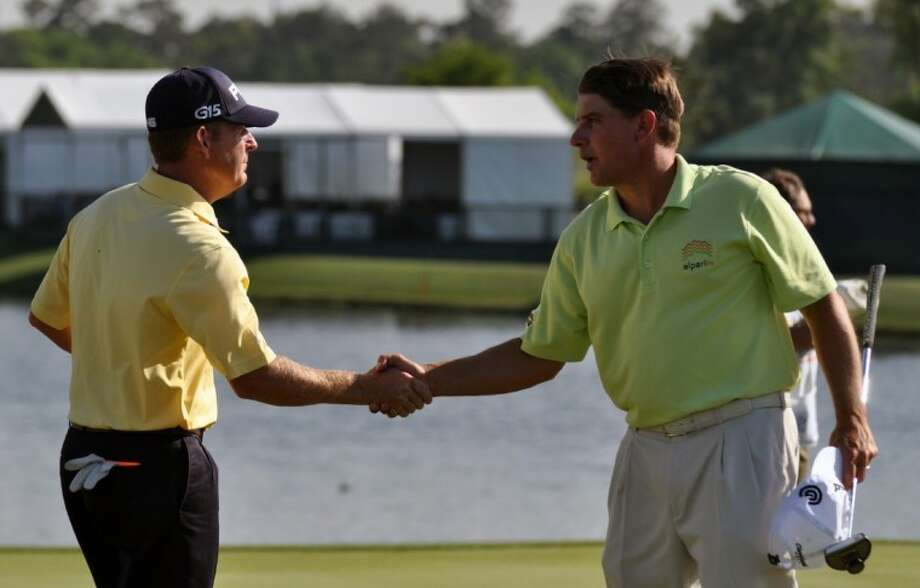 McCullough High School graduates Jeff Maggert, left, and Roland Thatcher shake hands after their round at the Shell Houston Open in Humble on Thursday.