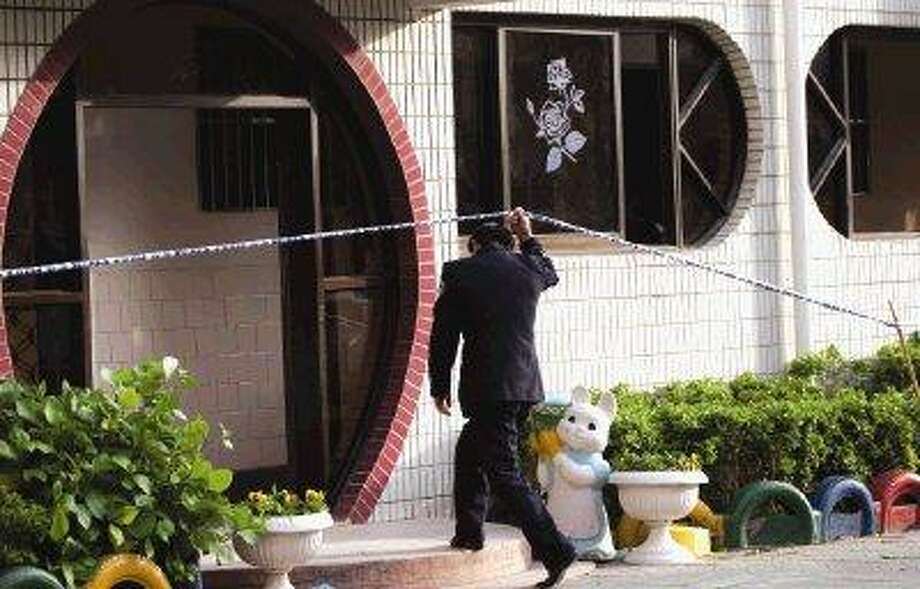A police officer crosses the police line to enter a building where students were attacked at the Zhongxin Kindergarten in Taixing, in east China's Jiangsu Province, Thursday. A knife-wielding man attacked a kindergarten class of 4-year-olds Thursday, slashing two dozen children in what an expert said was a copycat rampage of two other episodes at Chinese schools in the past month. / AP2010