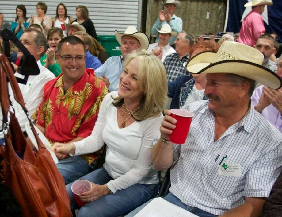 Darla Ostrander, center, of Montgomery, smiles as she bids on Matthew Duval's Grand Champion steer during the 2012 Montgomery County Fair Jr. Livestock Auction April 18 at the Montgomery County Fairgrounds in Conroe.
