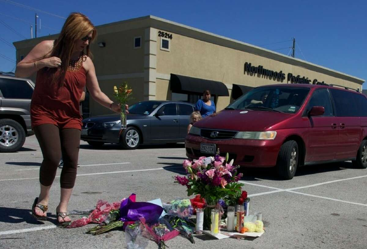 Geanette Smith, of Conroe, places flowers at a makeshift memorial for murder victim Kala Golden, 28, in the parking lot of the Northwoods Pediatric Center where Golden was gunned down Wednesday in The Woodlands.
