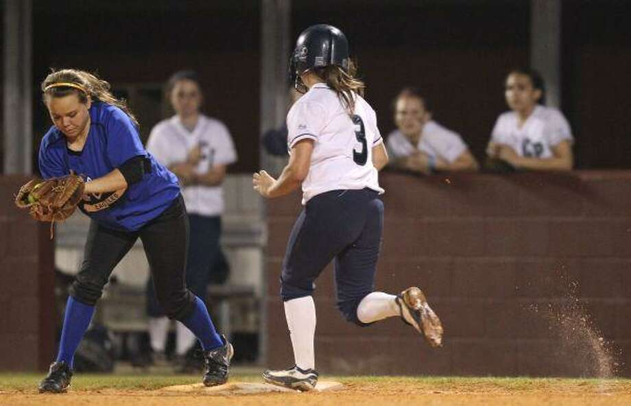 New Caney's Sarah Upchurch makes the catch as College Park's Shannon Fox runs into first during last Wednesday's game at College Park High School in The Woodlands. / The Courier